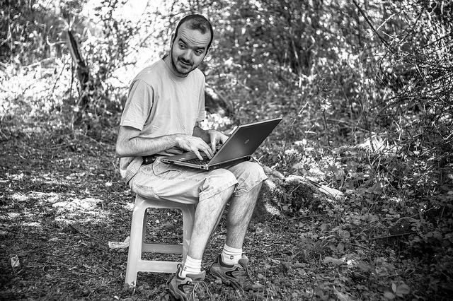 Mann mit Laptop im Garten